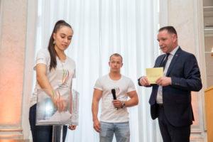 Unter der Leitung von Christian Schmid (Moderator, rechts) losten Tabea Alt (international ausgezeichnete Kunstturnerin) und Fabian Hambüchen (ehemaliger Kunstturner und Olympiasieger 2016 am Reck) die Wettkampftage für die IKA/Olympiade der Köche 2020 aus. Foto: Messe Stuttgart